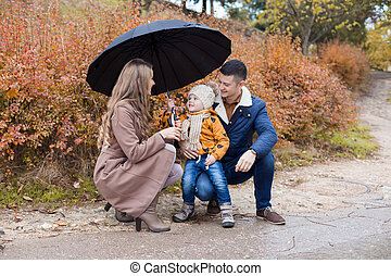 family autumn in the Park in the rain umbrella