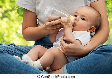 close up of mother feeding baby with milk formula