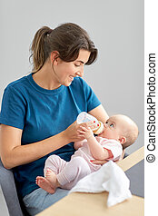 mother feeding baby daughter with milk formula