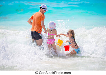 Family beach holidays. Father with kids have a lot of fun
