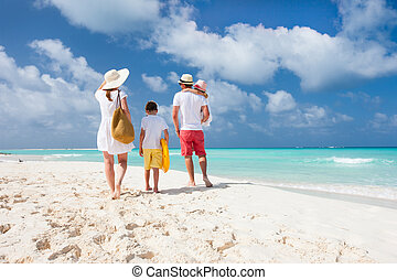 Family beach vacation - Back view of a happy family on ...
