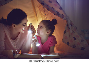 Family reading bedtime mom and child reading book with a stock family bedtime mom and child daughter are reading a book with flashlights in tent pretty young mother and lovely girl having fun in children room sciox Gallery