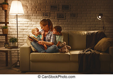Family before going to bed mother reads children book about lamp in evening