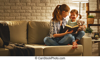 Family before going to bed mother reads to child daughter book near lamp in the evening