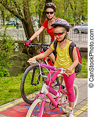 Family bike ride. Family wearing bicycle helmet with rucksack .
