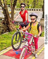 Family bike ride with rucksack cycling on bike lane.