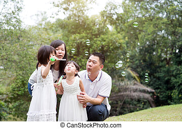 Family blowing soap bubbles