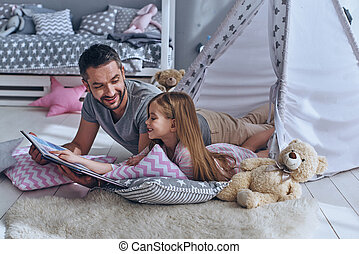 Family bonding. Father reading a book to his daughter while...