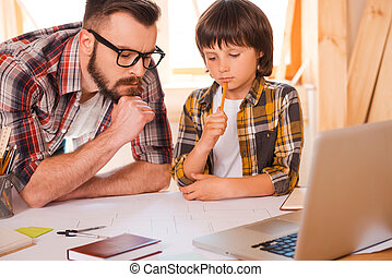 Family brainstorming. Thoughtful young man and his sonworking together while sitting at working place
