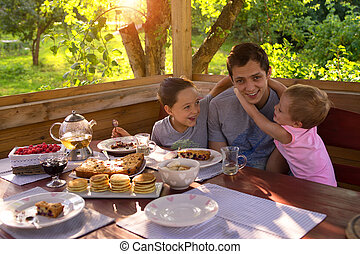 Family Breakfast in a country house. children happily cuddling with daddy