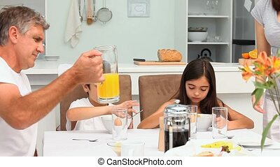 Family breakfast with orange juice and cereal in the dinning...