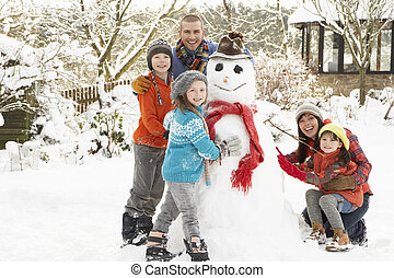 Family Building Snowman In Garden