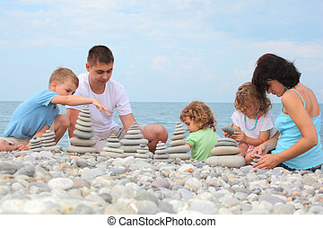 family builds  stone stacks on pebble beach