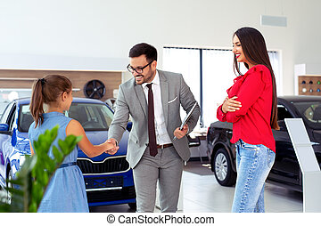 Family buying a new car in the car dealership saloon