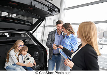 Family buying auto in dealership, manager giving car keys.