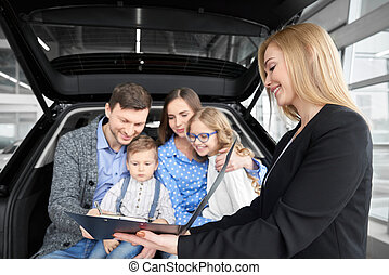 Family buying automobile, man signing document of purchase.