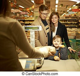 Family buying bread in a grocery store