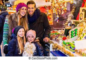 Family buying Christmas decoration on market