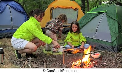 Family camping in the woods marshmallow roasts.
