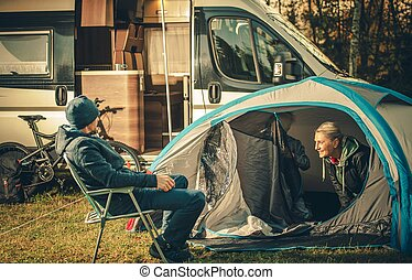 Family Camping Vacation. Motorhome and Tent on the Campsite. Caucasian Family.
