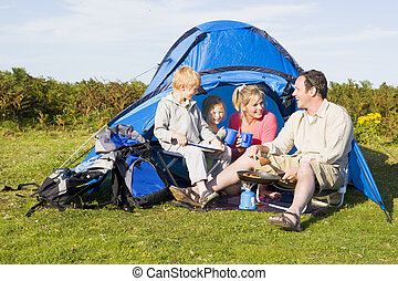 Family camping with tent and cooking