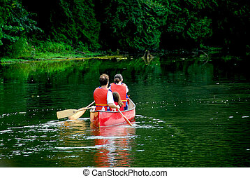Family canoe river - Family of three canoing on a calm green...
