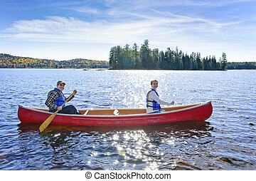 Family canoe trip - Family canoeing on sunny Lake of Two...