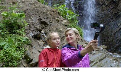 Family capturing themselves with small personal camera at mountain waterfall