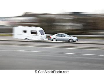 family car towing a caravan along the motorway