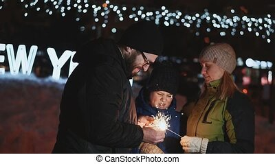 Family celebrates new year. Father lights Bengal lights. On the street night, winter time