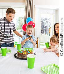 Family Celebrating Boy's Birthday At Home