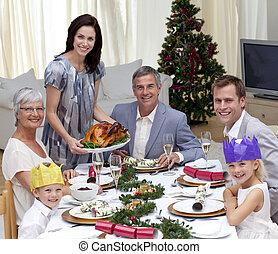 Family celebrating Christmas dinner with turkey