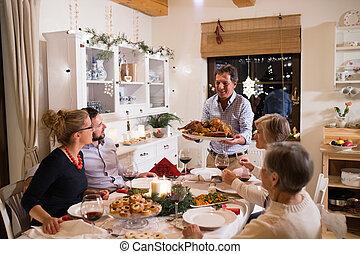 Family celebrating Christmas. Father bringing food.