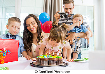 Family Celebrating Girl's Birthday At Home
