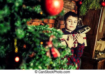 Family celebration of the New Year. Boy near Christmas tree.