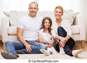 parents and little girl sitting on floor at home - family,...