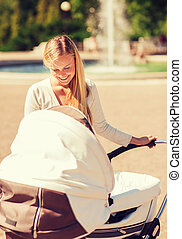 happy mother with stroller in park