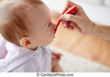 hand with spoon feeding little baby at home
