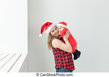 Family, childhood and Christmas concept - Young mother holding baby in santa suit indoor