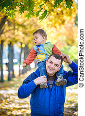 family, childhood and fatherhood concept. happy father carrying son with maple leaves over autumn park background. Autumn mood. Positive emotions. Lifestyle.