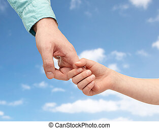 father and child holding hands over blue sky