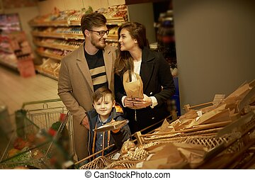 Family choosing bread in a grocery store