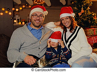 Family Christmas celebrates. Parents and their little son dressed in a Santa's hat.