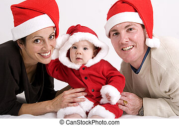 Family Christmas - Young couple with baby dressed in Santa...