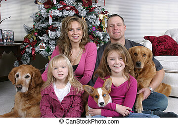 Family Christmas - smiling family and dogs sitting by...