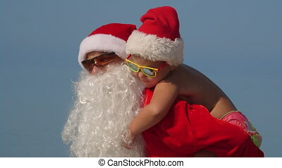 Family Christmas tropical beach vacation father Santa Claus with daughter