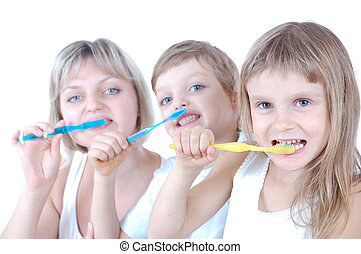 Two children and mother cleaning teeth over white background. Shallow field of depth. The focus is on the girl with a yellow toothbrush.