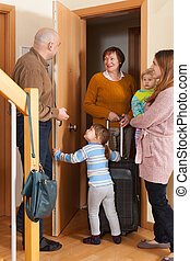 Family coming to grandmother with luggage