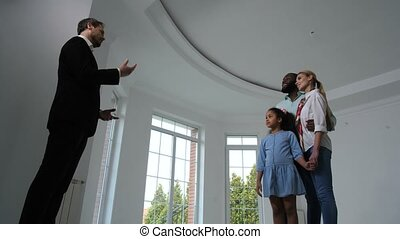 Family communicating with realtor showing house