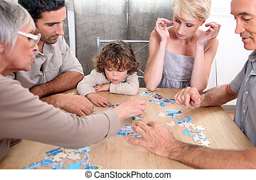 Family completing jig-saw puzzle